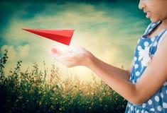 Att ta för liten flicka att bry sig röd origami för ett flygplanpapper Arkivbilder