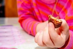 Att ?ta f?r liten flicka flinar chokladst?ngen f?r frukost royaltyfri bild