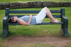 Att ta sig en tupplur på parkerar bänken Arkivbild