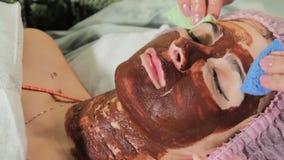 Att tvätta av chokladen på flicka`en s vända mot med en svamp chokladSpa terapi close upp arkivfilmer
