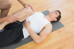 Att undersöka för fysisk terapeut som är ungt, mans benet Arkivfoto