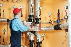 Att värma iscensätter repairmanen i kokkärlrum Royaltyfri Bild