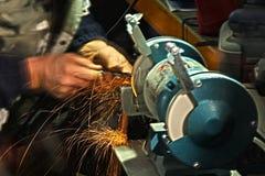 Att vässa för arbetare bearbetar på en grinder Royaltyfri Bild