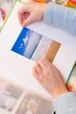 Attaccando le immagini all'album di foto Fotografie Stock