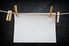 Attaccatura di carta per appunti in bianco sulla corda con le mollette per il bucato Fotografie Stock