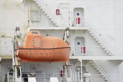 Attachés oranges d'un bateau de secours à un grand bateau blanc Images libres de droits