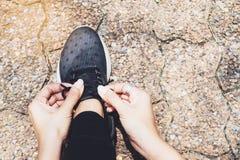Attachant des chaussures de sport, femme asiatique étant prête pour courir, sport en plein air photos libres de droits