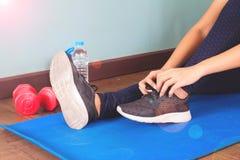 Attachant des chaussures de sport, femme asiatique étant prête pour la formation de poids Exercice, formation de forme physique S image stock