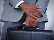 Attache. Close-up of businessman with briefcase in hand isolated on grey background stock image