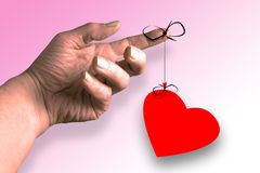 Attached. Finger and heart string stock image
