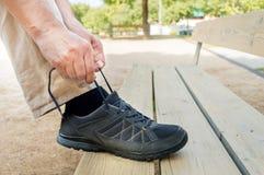 Attachement de sa chaussure sur un banc Image stock