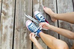 Attachement des dentelles des espadrilles de jeans sur le plancher en bois Photographie stock