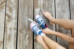 Attachement des dentelles des espadrilles de jeans sur le plancher en bois Photo libre de droits