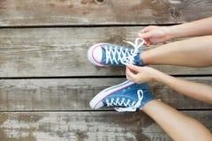 Attachement des dentelles des espadrilles de jeans sur le plancher en bois Images libres de droits