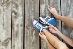 Attachement des dentelles des espadrilles de jeans sur le plancher en bois Image stock