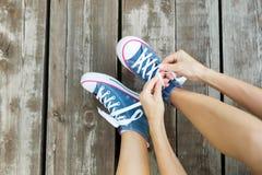 Attachement des dentelles des espadrilles de jeans sur le plancher en bois Image libre de droits