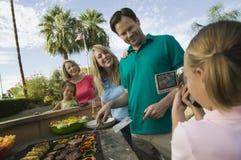 Attacher du ruban adhésif visuel de la fille (7-9) parents la soeur de grand-mère (7-9) au barbecue extérieur. photos libres de droits