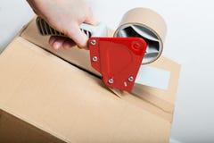 Attachez du ruban adhésif au distributeur d'arme à feu Photographie stock