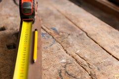 Attachez du ruban adhésif au mesureur, conseil en bois, crayon jaune photos stock