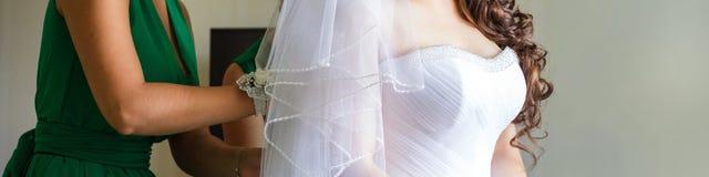 Attachez un corset la jeune mariée Photo libre de droits