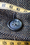 Attaching of button to green tweed jacket. By needle close up Stock Images