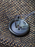 Attaching of button to green tweed by needle Royalty Free Stock Photo