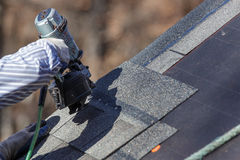 Attaching shingles to the roof. Stock Photos