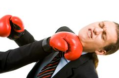 Attack. Portrait of defeated businessman in boxing gloves being hit by opponent Stock Photography