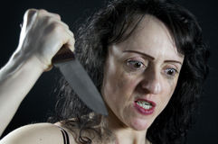 Attack. Crazed woman stabbing with a large kitchen knife Stock Images