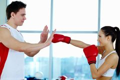 Attack. Portrait of young women in red boxing gloves showing attack grip to trainer Royalty Free Stock Photography