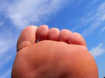 Attack of the 50 ft. Foot. The sun shines on a beautiful woman's sandy, oddly shaped, and mildly chubby foot with a cloudy blue sky background Stock Photography
