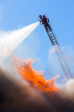 Attack from above. A fireman streams a blast of water from an aerial pump ladder high above a raging fire royalty free stock images