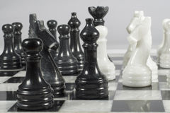 Attack of the black pieces in the course of a chess match. Marble chess board Royalty Free Stock Images
