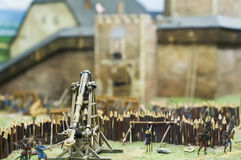 Attack to a Castle. Miniature of a medieval Battle with Catapult and soldiers Royalty Free Stock Images