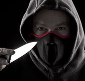 Attacker. Man with a knife and mouth cover royalty free stock image