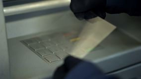 Attacker stealing personal code by removing fingerprints from atm keyboard. Stock photo royalty free stock images