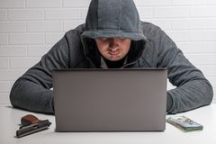 The attacker steals personal data in the computer, the hacker. In the hood at work royalty free stock photos