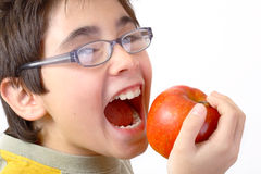 Attacking the apple. Boy with glasses on eating an apple Stock Photo