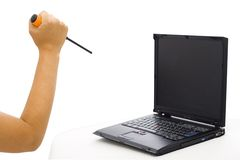 Attacking the laptop 1. A woman attacking the laptop whit a screw-driver Royalty Free Stock Photography