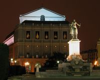 Attacking the teather. A night shot of a statue and the teather house in madrid spain Royalty Free Stock Images