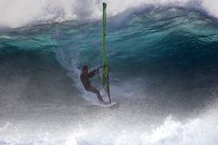 Attacking water. Big wave windsurfing against sunlight Royalty Free Stock Photo
