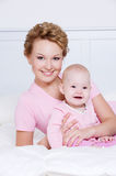 Attactive mother lying with her baby on the bed Royalty Free Stock Photos