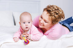 Attactive mother lying with her baby on the bed Stock Photography