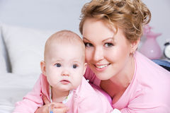 Attactive mother lying with her baby on the bed Stock Photo