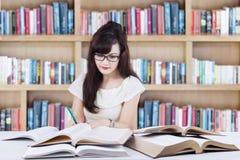 Attactive uczeń robi szkolnemu zadaniu w bibliotece Zdjęcie Stock