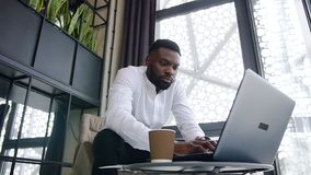 Attantive clever dark-skinned office worker with well-groomed beard working at the computer in the special separate