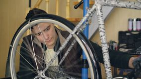Attantive mechanic in casual clothes and gloves is checking bicycle wheel turning it and looking at mechanism. Bike. Attantive male mechanic in casual clothes stock video