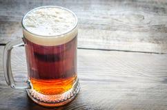 Attaquez avec de la bière foncée sur la table en bois image stock