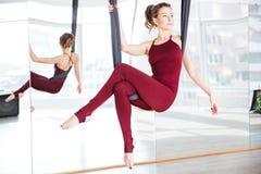 做空中瑜伽的姿势Attarctive妇女使用吊床 免版税库存照片