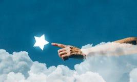 Atteignez et touchez l'étoile photo stock